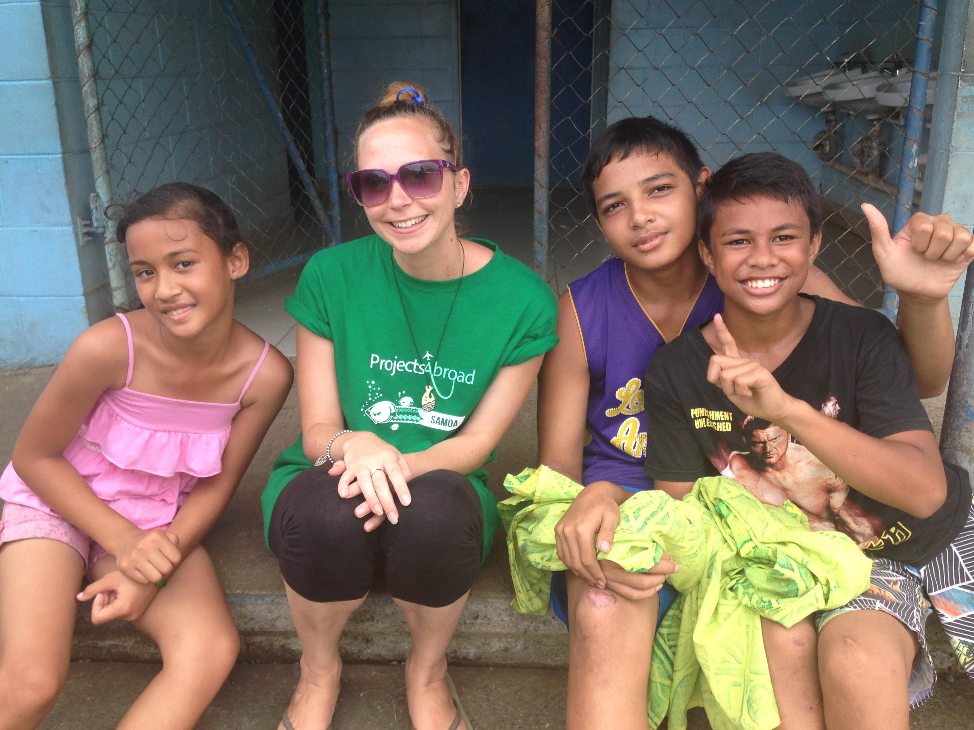 A Childcare volunteer in Samoa poses for a picture with children at her placement